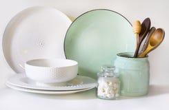Lerkärl, bordsservis, redskap och annat olikt vit och turkosmaterial på vit bordsskiva Kökstilleben som bakgrund f arkivbild