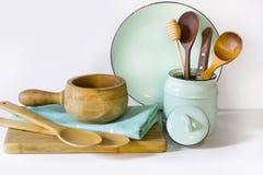 Lerkärl, tappningbordsservis, redskap och annat olikt vit och turkosmaterial på vit bordsskiva Kökstilleben som tillbaka royaltyfria bilder