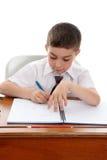Lernbegieriger Junge, der Schulearbeit erledigt lizenzfreies stockfoto