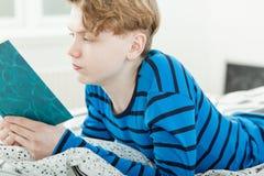 Lernbegieriger junger Teenager, der ein Buch liest Stockbilder