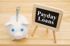 Lernen über Zahltagdarlehen mit einem Sparschwein stockfotos