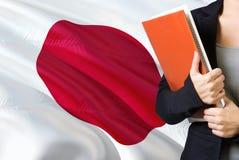 Lernen des japanische Sprachkonzeptes Stellung der jungen Frau mit der Japan-Flagge im Hintergrund Lehrer, der Bücher, Orange häl stockfoto