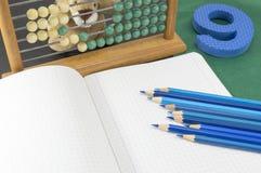 Lernen des Kalküls Blaue Zahl 9 des alten Taschenrechners und Bleistifte Stockfoto