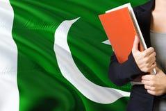 Lernen des pakistanischen Sprachkonzeptes Stellung der jungen Frau mit der Pakistan-Flagge im Hintergrund Lehrer, der Bücher, Ora stockbilder