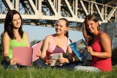 Lernen mit drei Freundinnen im Freien Stockfotos