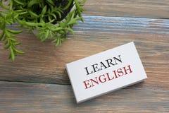 Lernen Sie den englischen Text, der auf Notizbuchseite, roten Bleistift und Kaffeetasse geschrieben wird Schreibtischtischplattea Stockfoto