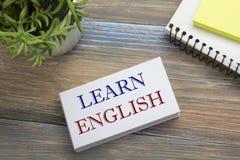 Lernen Sie den englischen Text, der auf Notizbuchseite, roten Bleistift und Kaffeetasse geschrieben wird Schreibtischtischplattea Stockfotos