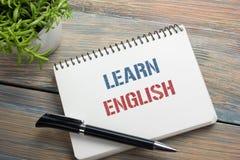 Lernen Sie den englischen Text, der auf Notizbuchseite, roten Bleistift und Kaffeetasse geschrieben wird Schreibtischtischplattea Stockfotografie