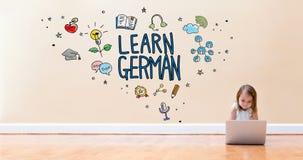 Lernen Sie deutschen Text mit dem kleinen Mädchen, das eine Laptop-Computer verwendet Lizenzfreies Stockfoto