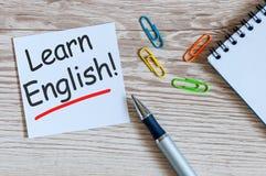 Lernen Sie Englisch - Anmerkung am hölzernen Hintergrund mit Lehrergläsern lizenzfreie stockbilder