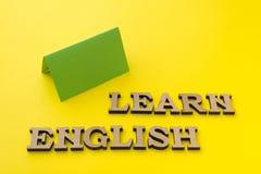 Lernen Sie Englisch, Wörter in den hölzernen Buchstaben mit gelbem Hintergrund lizenzfreie stockbilder