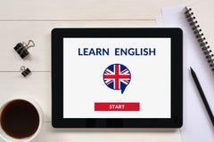 Lernen Sie online englisches Konzept auf Tablettenschirm mit Bürogegenstand stockfotografie