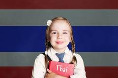 Lernen Sie thailändische Sprache Thailand-Konzept mit Kinderkleiner Studentin mit rotem Buch gegen den Thailand-Flaggenhintergrun stockbild