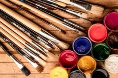 Lernen Sie, wie man malt Mehrfarbige Gouachefarbe in den offenen Behältern und in den künstlerischen Bürsten auf einem hölzernen  Lizenzfreie Stockbilder