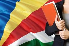 Lernen Sprachkonzeptes des von den Seychellen Stellung der jungen Frau mit der Seychellen-Flagge im Hintergrund Lehrer, der Büche lizenzfreie stockfotos