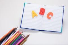 Lernkonzept mit Buch, Buchstaben und Bleistiften Stockfoto