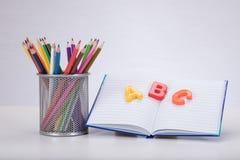 Lernkonzept mit Buchstaben, Buch und Bleistiften Stockfoto
