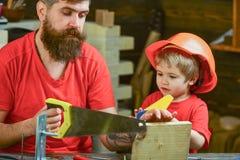 Lernspielkonzept Junge, Kind beschäftigt im Schutzhelm lernend, Handsaw mit Vati zu benutzen Vater, Elternteil mit Stockfoto