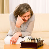 Les échecs aînés de pièce de femme heureux se reposent sur le sofa Photos libres de droits