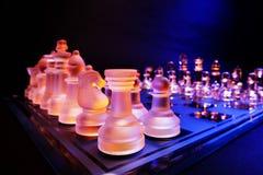 Les échecs en verre sur un échiquier se sont allumés par la lumière bleue et orange Photos stock