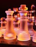 Les échecs en verre sur un échiquier se sont allumés par la lumière bleue et orange Photo stock