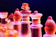 Les échecs en verre sur un échiquier se sont allumés par la lumière bleue et orange Image libre de droits