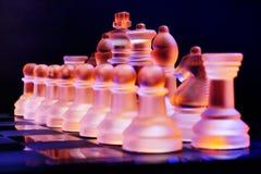 Les échecs en verre sur un échiquier se sont allumés par la lumière bleue et orange Images libres de droits