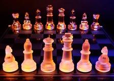 Les échecs en verre sur un échiquier se sont allumés par la lumière bleue et orange Photographie stock libre de droits