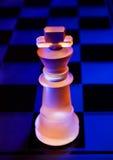 Les échecs en verre sur un échiquier se sont allumés par la lumière bleue et orange Photo libre de droits