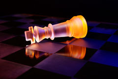 Les échecs en verre sur un échiquier se sont allumés par la lumière bleue et orange Image stock