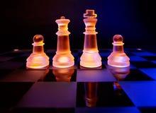 Les échecs en verre sur un échiquier se sont allumés par la lumière bleue et orange Images stock