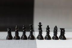 Les échecs figurent prêt pour la bataille sur le premier plan noir et blanc Images libres de droits