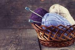 Les écheveaux ont coloré des aiguilles de fil et de tricotage dans un panier Image stock