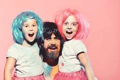 Les écolières et l'homme avec la barbe ont des taches de peinture sur des visages photo stock