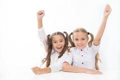 Les écolières heureuses gardent des mains tandis que reposez-vous au fond de blanc de bureau Jeu-concours d'école de victoire Ils photographie stock libre de droits