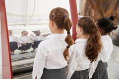 Les écolières regardant dans un miroir incurvé une science centrent photographie stock