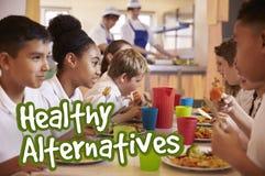 Les écoliers mangent les repas alternatifs sains Images libres de droits