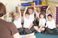 Les écoliers soulèvent leur main dans une classe primaire Photographie stock