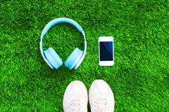 Les écouteurs bleus et le smartphone blanc avec des chaussures d'espadrilles de sports sur une herbe verte ont donné au fond une  Photo stock