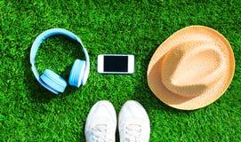 Les écouteurs bleus et le smartphone blanc avec le chapeau de paille sur une herbe verte ont donné au fond une consistance rugueu Image stock