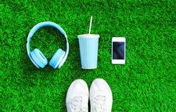 Les écouteurs bleus, le smartphone blanc, tasse de jus de fruit avec des chaussures d'espadrilles de sports sur une herbe verte o Photographie stock libre de droits
