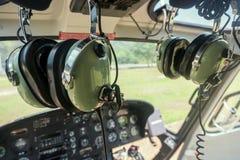 Les écouteurs du pilote d'hélicoptères ont monté dans la carlingue avec le tableau de bord photos stock