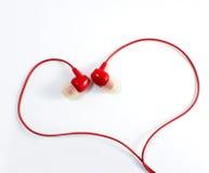 Les écouteurs rouges au coeur forment, aiment, musique Photo stock