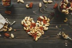 Les écrous se mélangent dans la forme de coeur sur la table en bois Les écrous se mélangent aux graines et aux fruits secs sur la image libre de droits