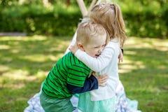 Les élèves du cours préparatoire d'enfants embrassent et jouent en parc Fille et garçon Photos stock