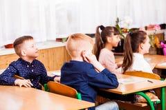 Les élèves mignons écoutent leur professeur sur la leçon Image stock