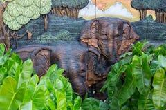 Les éléphants lapident la sculpture sur le mur avec le fond de jungle dedans Image stock
