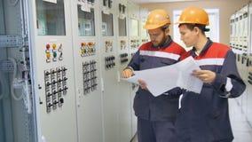 Les électriciens montent à l'armoire d'alimentation de réseau et au bouton-poussoir banque de vidéos