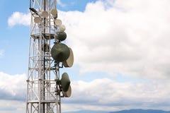 Les émetteurs et les antennes sur la télécommunication dominent avec le ciel bleu nuageux Photos libres de droits