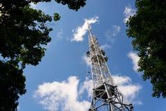 Les émetteurs et les antennes sur la télécommunication dominent avec le ciel bleu nuageux Photos stock